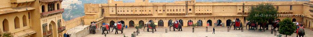 Touristen beim Elefantenreiten in den Hof vom Palast wo man links am Bildrand aussteigen soll bei der Rajasthan Rundreise durch Indien.