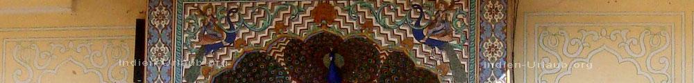 Mystische Wesen die auf dem Ruecken von Pfauen reiten auf den Mosaiken zu sehen am Eingagnsportal der Residenz der Fuerstenfamilie vom Stadtpalast in Jaipur bei der Rajasthan Rundreise.